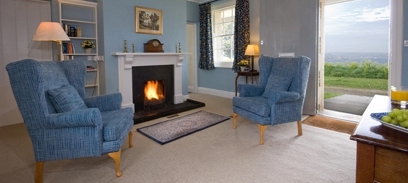 Photo of armchairs and fireplace with coastal view in The Captain's Quarter.