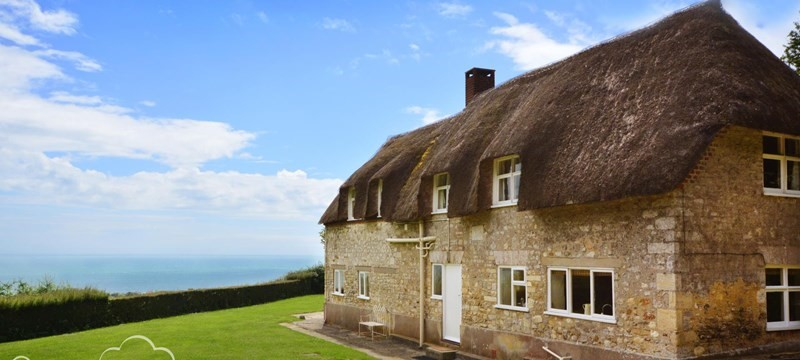 Photo of one of the Dream Cottages with thatched roof.
