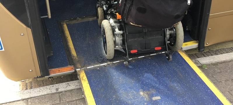 Picture of a wheelchair user going up a ramp onto the bus.