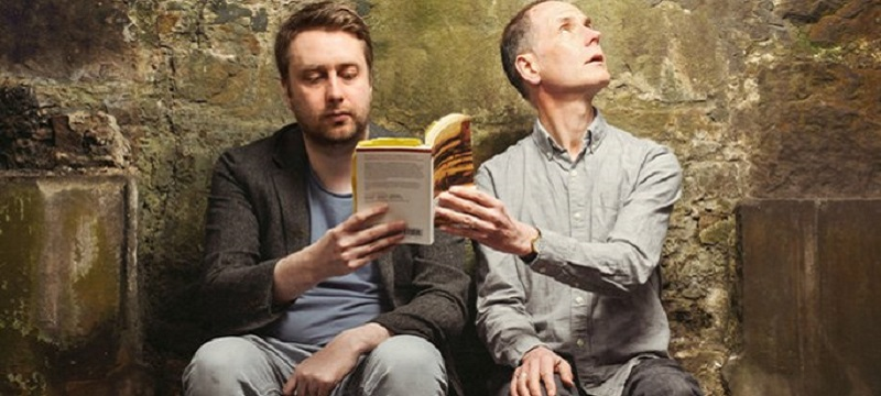 Photo from the production of Our Fathers showing two men holding a book.