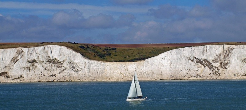 Photo of the white cliffs of Dover and a yacht.