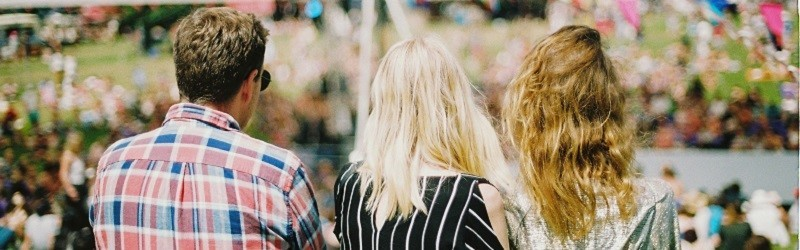 Photo of three people at a festival.