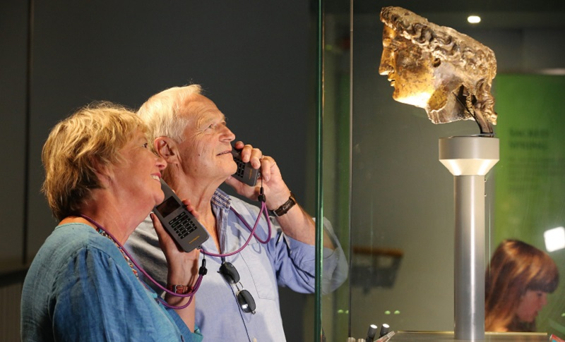 Photo of a couple using audio guides at the Roman Baths.