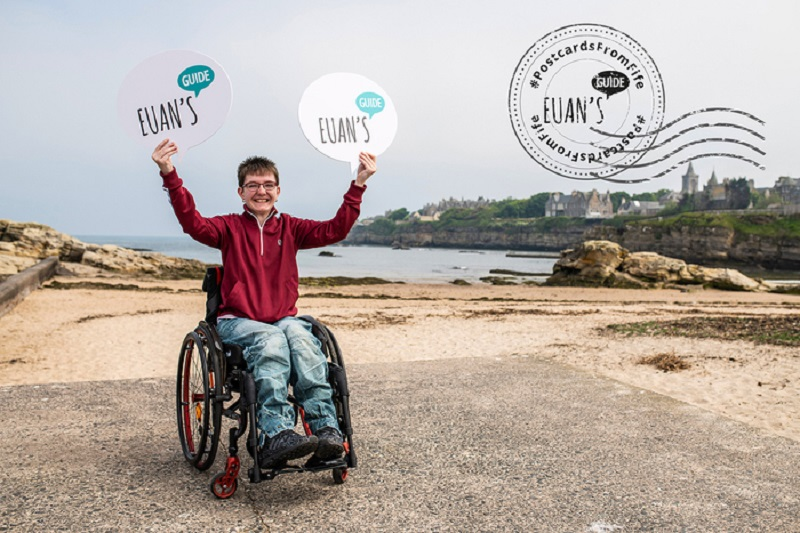 A postcard from Fife showing Chelsea, a wheelchair user, at the beach in St Andrews holding Euan's Guide logos.