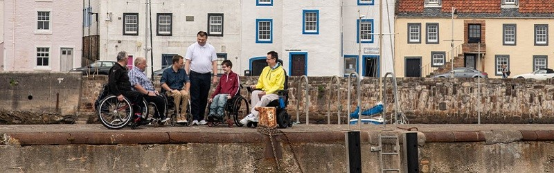 Photo of Euan's Guide Ambassadors on a harbour in Fife.