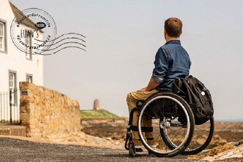 Postcard of Ryan, a wheelchair user, looking at St Monans Windmill.