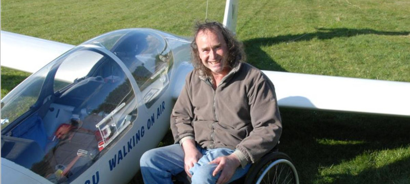 Photo of a glider next to a pilot sitting in a wheelchair.