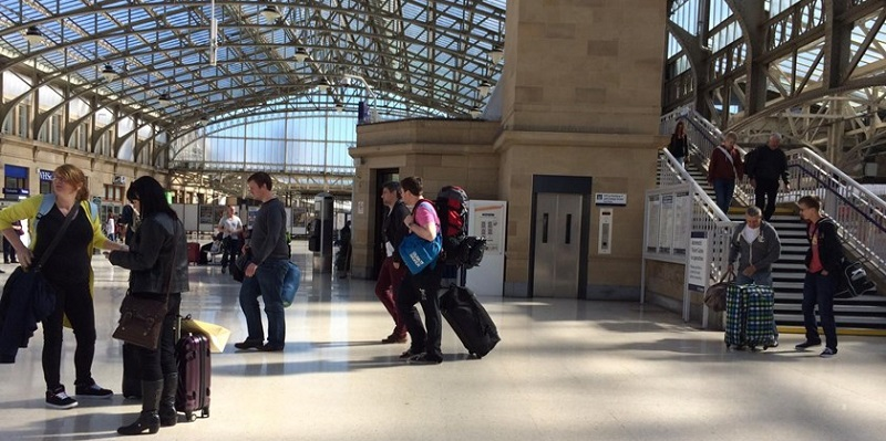 Photo of crowd walking in train station with suitcases.