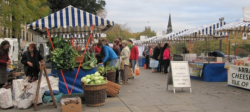 Photo of Edinburgh's market outdoor cheese and vegetable stalls and people shopping.
