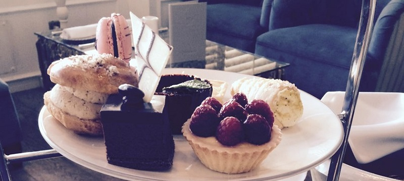 Photo of a tray with six different sweet treats, including a raspberry pie and a macaroons.