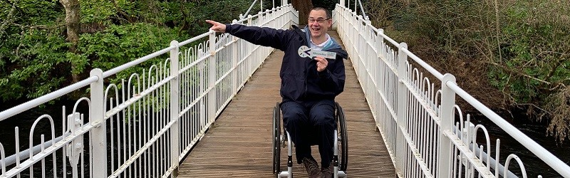 Photo of Paul Ralph holding a Disabled Access Day arrow on a suspension bridge.