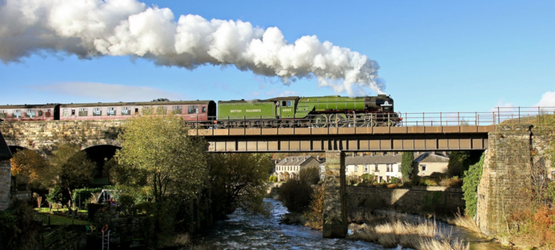 Photo of a steam locomotive crossing a bridge on the East Lancashire Railway.