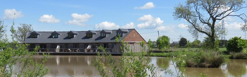 Photo of a row of cottages by a lake on a sunny day.