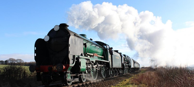 Photo of a steam locomotive traveling through the Hampshire countryside on a sunny day.