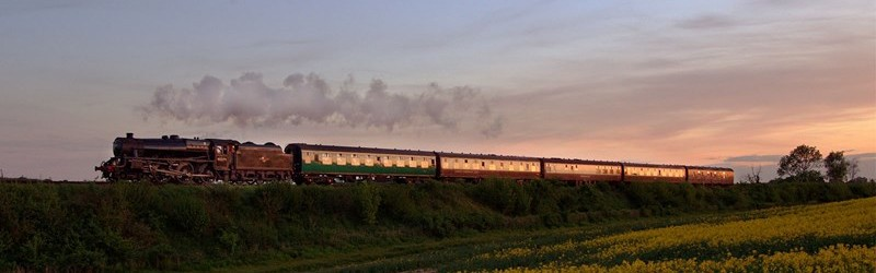 Photo of a steam locomotive pulling passenger carriages on the Mid Hants Railway.