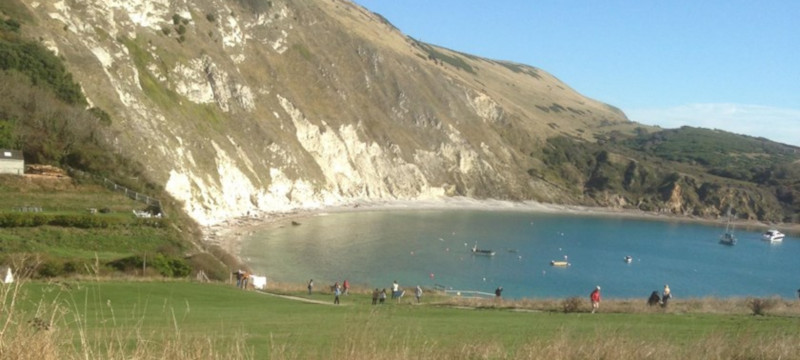 Photo of Lulworth Cove in sunny weather.