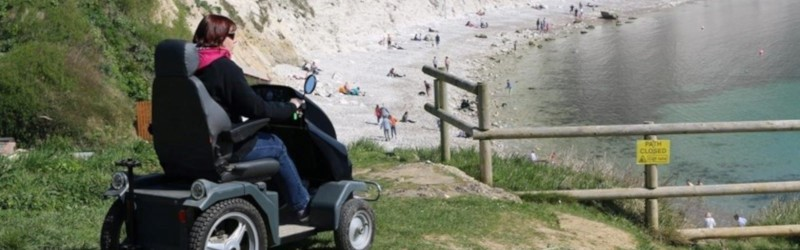 Photo of a woman using an off-road mobility scooter at Lulworth Cove, England.