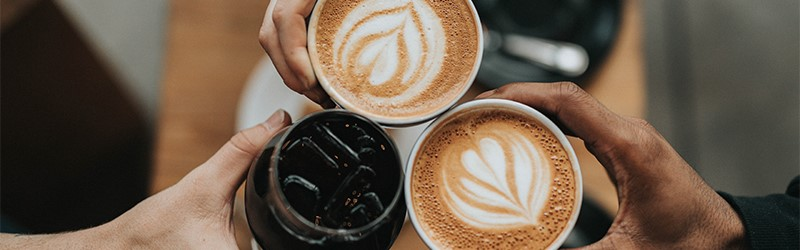 Photo of hands holding coffee.