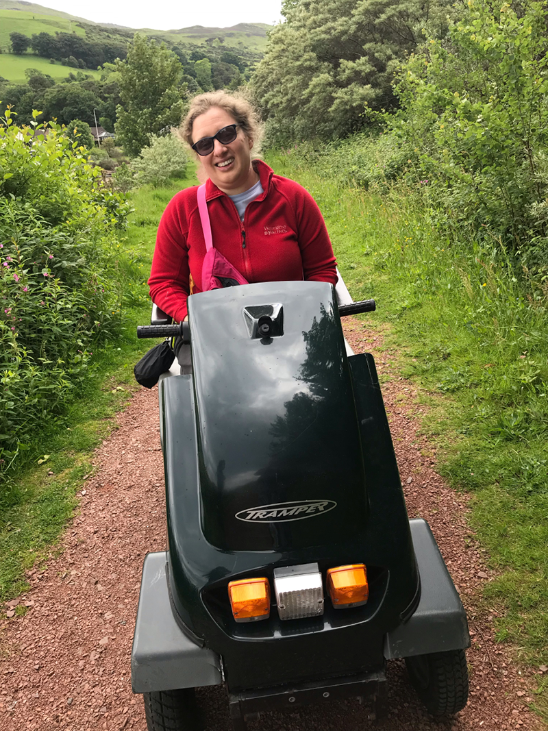Photo of Zoe using an all terrain mobility scooter.