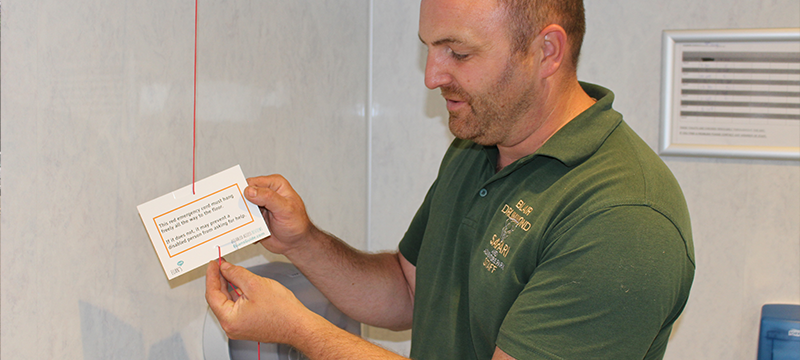 member of staff putting a Red Cord Card on the emergency red cord at Blair Drummond Safari & Adventure Park