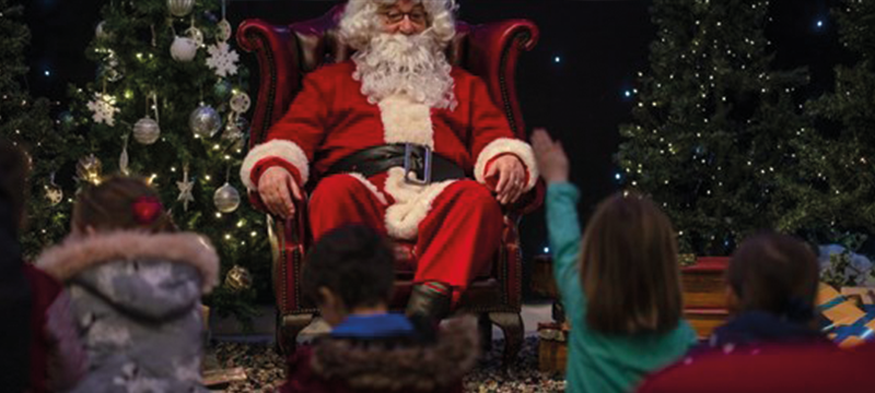 Image of Santa sitting on a chair with children around him