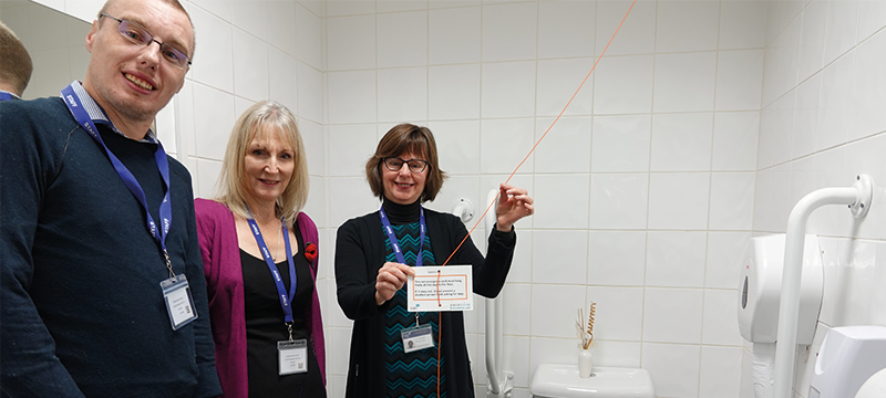 Staff at Disability Action Yorkshire showing their red emergency cord in their accessible toilet
