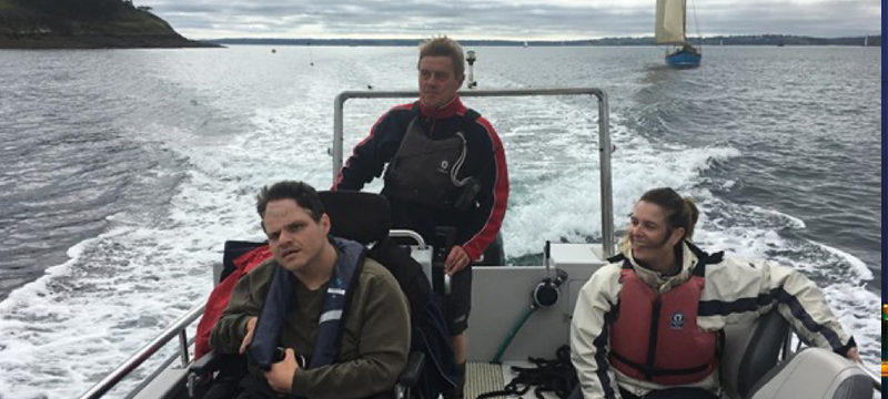 Image of three people including on wheelchair user on a sailboat
