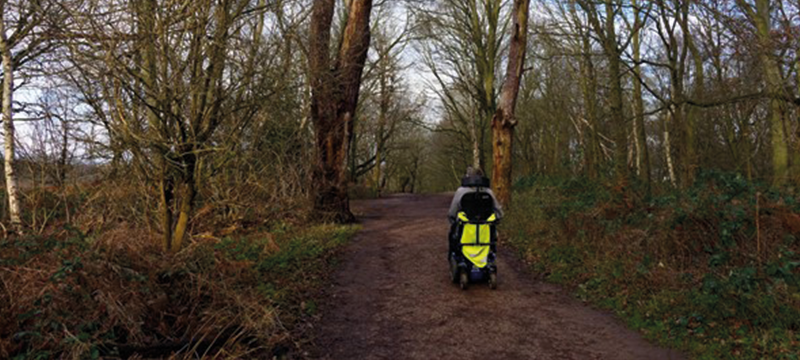 A power chair user pictured travelling along a forest path