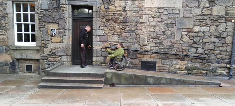 Image of wheelchair user going up a ramp at Edinburgh Castle