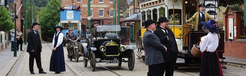 Image of character performers in an old looking town with tram cars and carts.