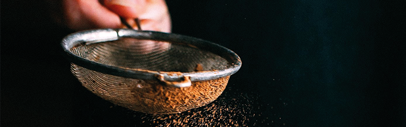 Image of someone sifting cocoa powder