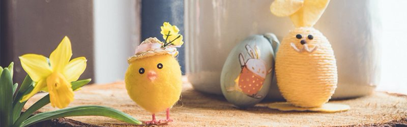 image of an egg painted to look like a bunny sitting next to a small plastic chick and yellow flower on a wooden table. The table is against a bright window.