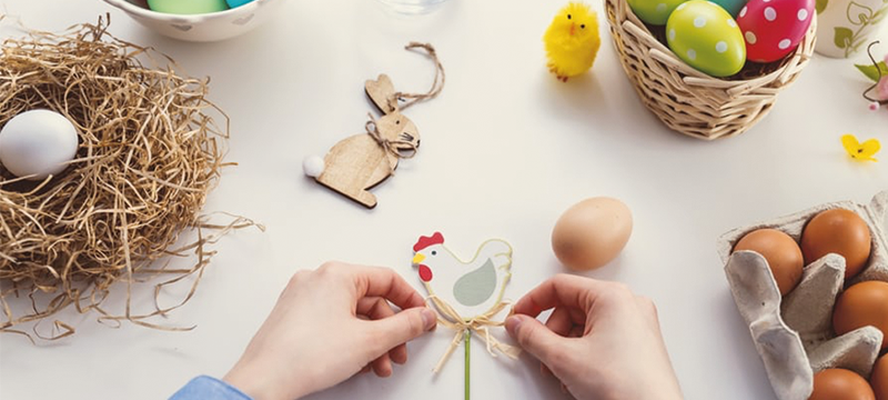 Image of hands creating an Easter craft - a cut out of a cartoon chicken on a stick. Also on the table is a nest, some eggs and a wooden bunny rabbit.