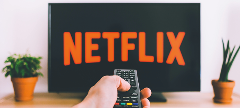 Image of a hand pointing a TV remote at a TV screen that has the Netflix logo in red.