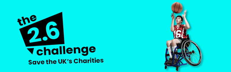 "Blue background with a young boy in a sports wheelchair playing basketball on the right hand side. On the left side, the words 'The 2.6 Challenge: Save the UK's charities"" is in black."