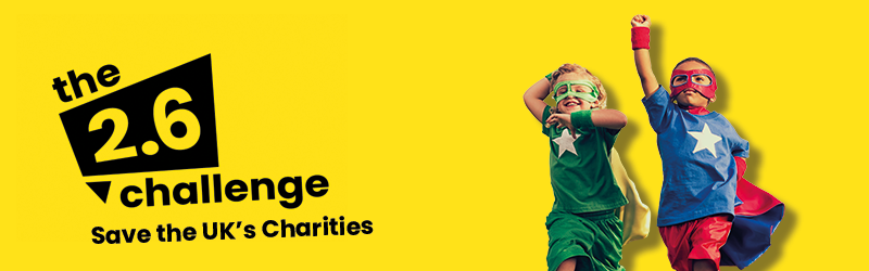 Yellow background image with The 2.6 Challenge logo. On the right hand side there is an image of two boys dressed as superheroes.