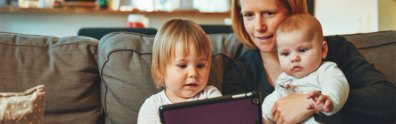 Image of a mum on a couch with her children looking at an iPad