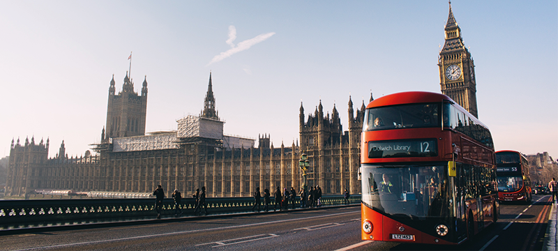 Image of a red bus on a road in front of Big Ben and the Palace of Westminster.