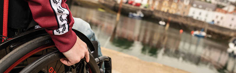 Image of a wheelchair user by a body of water.