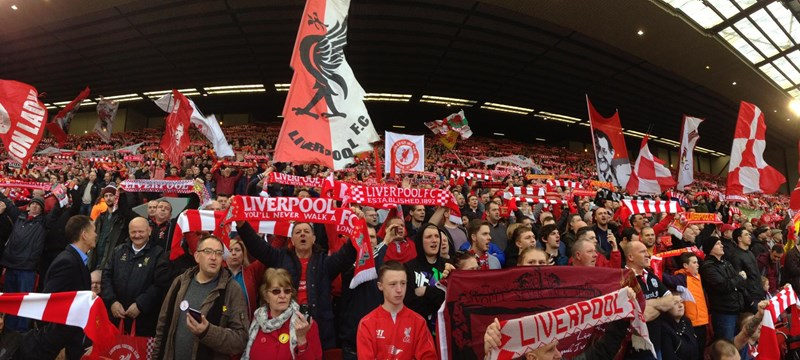 Image of Liverpool Football Club fans holding up scarves.