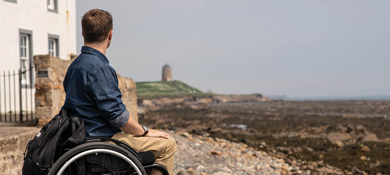 Image of a wheelchair user by the beach
