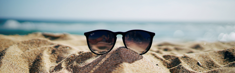An image of sunglasses lying on a beach