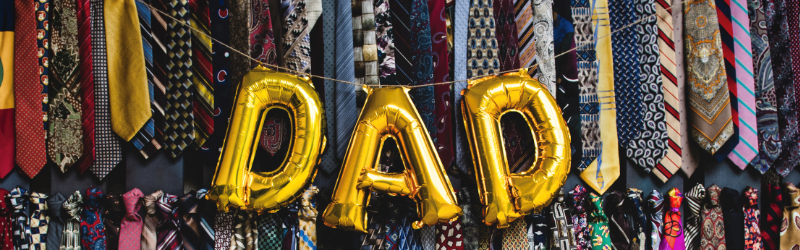An image of a balloon banner spelling out Dad, in the background there is a wall of ties in various colours.
