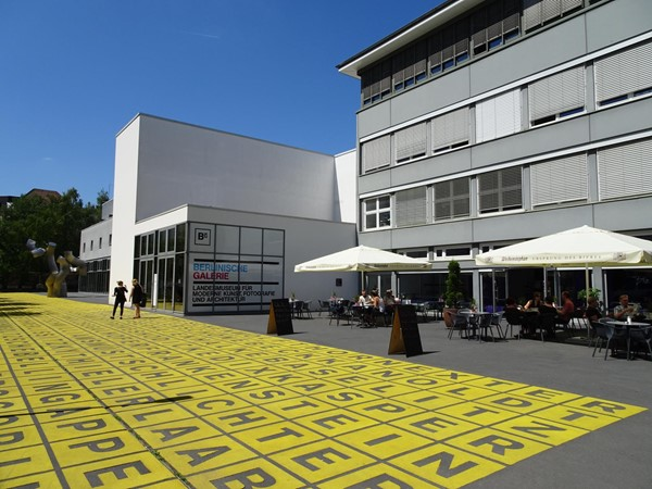 Image of the outside of the Berlinische Galerie, there are tables and chairs out front