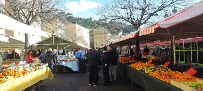Image of a market in Nice, there are stalls on either side selling various vegetables and fruits.