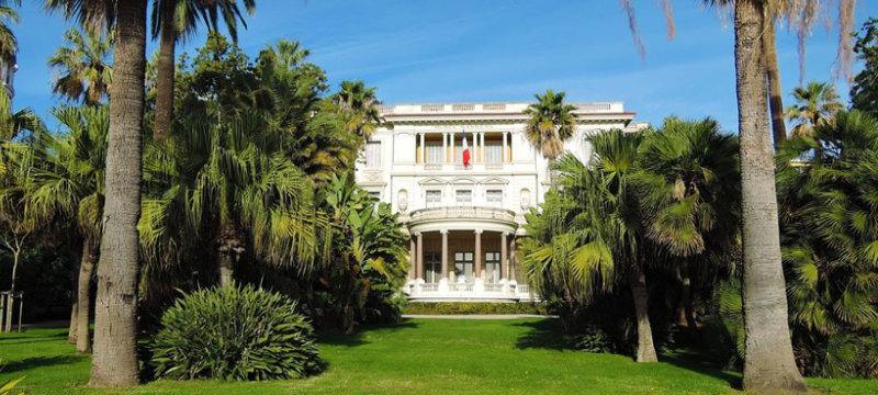 Exterior image of Musée Masséna, there are many palm trees in the garden in front of the building.