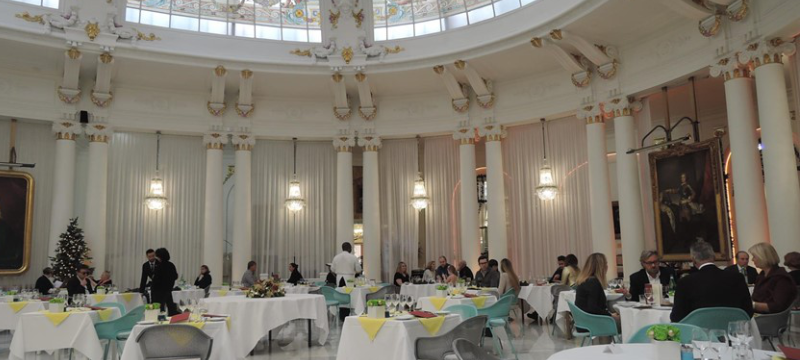 Image of a white fancy dining hall with various chairs and tables arranged in a circle.