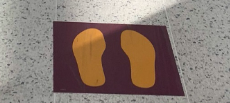 Sticker of footsteps on the floor showing people where to stand