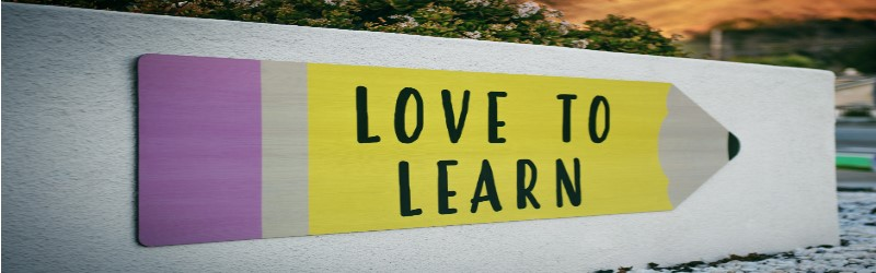 An image of sign with the words 'Love to Learn' written on, along with the image of a pencil.