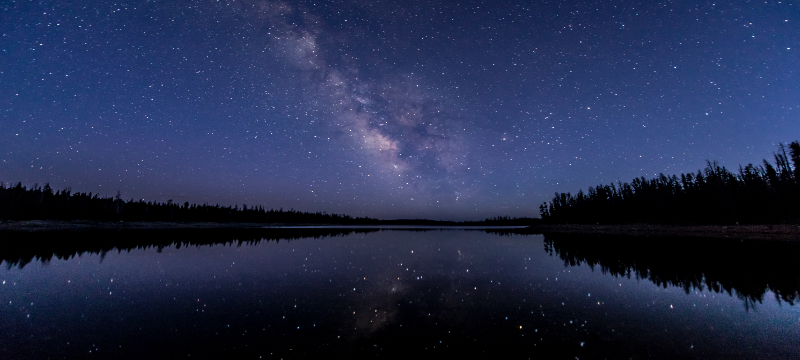 Image of the night sky over a lake that is reflecting the stars.